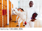 Купить «Active african american male fencer in uniform standing with mask and foil at fencing room», фото № 30680396, снято 11 июля 2018 г. (c) Яков Филимонов / Фотобанк Лори
