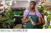 Купить «Forist spraying potted flowers», фото № 30680416, снято 14 февраля 2019 г. (c) Яков Филимонов / Фотобанк Лори