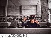 Купить «Woman gesturing while using virtual reality simulator », фото № 30682148, снято 26 мая 2019 г. (c) Wavebreak Media / Фотобанк Лори