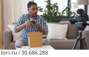 Купить «male blogger taking smartphone out of parcel box», видеоролик № 30686288, снято 26 апреля 2019 г. (c) Syda Productions / Фотобанк Лори