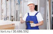Contractor mounting drywall with screw gun. Стоковое фото, фотограф Яков Филимонов / Фотобанк Лори