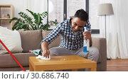 Купить «indian man cleaning table with detergent at home», видеоролик № 30686740, снято 26 апреля 2019 г. (c) Syda Productions / Фотобанк Лори