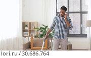 Купить «man with vacuum cleaner calling on cell at home», видеоролик № 30686764, снято 26 апреля 2019 г. (c) Syda Productions / Фотобанк Лори