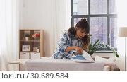 Купить «asian woman ironing bed linen at home», видеоролик № 30689584, снято 25 апреля 2019 г. (c) Syda Productions / Фотобанк Лори