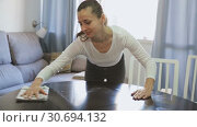Young woman cleans the table at home. Стоковое видео, видеограф Яков Филимонов / Фотобанк Лори