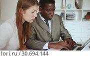 Купить «Young woman and man colleagues working with laptop and papers in office», видеоролик № 30694144, снято 26 апреля 2019 г. (c) Яков Филимонов / Фотобанк Лори
