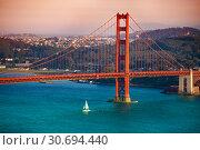 Yacht passing under Golden Gate Bridge at sunset (2015 год). Стоковое фото, фотограф Сергей Новиков / Фотобанк Лори