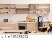 Купить «Aged contractor repairman working in the kitchen», фото № 30695552, снято 20 декабря 2018 г. (c) Elnur / Фотобанк Лори