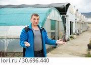 Купить «Farmer welcoming to greenhouse», фото № 30696440, снято 9 апреля 2019 г. (c) Яков Филимонов / Фотобанк Лори
