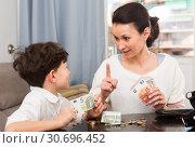 Купить «Woman giving money and admonishing boy», фото № 30696452, снято 28 марта 2019 г. (c) Яков Филимонов / Фотобанк Лори