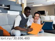Купить «Adult woman with her husband are holding folder with prices for furniture», фото № 30696480, снято 19 февраля 2018 г. (c) Яков Филимонов / Фотобанк Лори