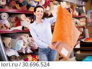 Купить «Positive woman customer choosing colorful carpet», фото № 30696524, снято 22 ноября 2017 г. (c) Яков Филимонов / Фотобанк Лори