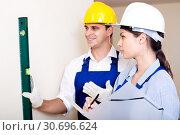 Купить «Constructor showing assistant measuring the wall», фото № 30696624, снято 28 января 2020 г. (c) Яков Филимонов / Фотобанк Лори