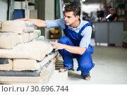 Купить «serious male in uniform is choosing cement in the building store», фото № 30696744, снято 26 июля 2017 г. (c) Яков Филимонов / Фотобанк Лори