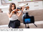 Купить «Female beautiful blogger playing violin», фото № 30697324, снято 1 октября 2018 г. (c) Elnur / Фотобанк Лори