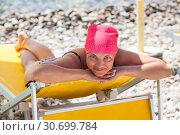 Купить «Улыбающаяся счастливая женщина загорает под зонтиком на галечном пляже», фото № 30699784, снято 23 июля 2018 г. (c) Кекяляйнен Андрей / Фотобанк Лори