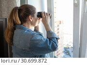 Купить «Взрослая женщина подсматривает за соседями в окно в бинокль из комнаты», фото № 30699872, снято 16 апреля 2019 г. (c) Кекяляйнен Андрей / Фотобанк Лори