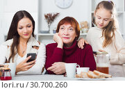 Купить «Bored grandma with daughter and granddaughter looking at phones», фото № 30700260, снято 25 ноября 2017 г. (c) Яков Филимонов / Фотобанк Лори