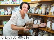 Купить «Glad mature female customer holding with cereal», фото № 30700316, снято 20 июня 2019 г. (c) Яков Филимонов / Фотобанк Лори