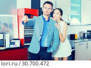 Купить «Young respectable man with smiling girlfriend in furniture store», фото № 30700472, снято 15 июня 2017 г. (c) Яков Филимонов / Фотобанк Лори