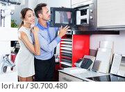 Купить «Couple choosing microwave in household appliance section», фото № 30700480, снято 15 июня 2017 г. (c) Яков Филимонов / Фотобанк Лори