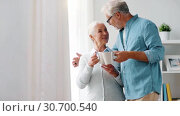 Купить «happy senior couple drinking coffee at home», видеоролик № 30700540, снято 23 мая 2019 г. (c) Syda Productions / Фотобанк Лори