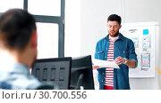 Купить «male ui designer showing user interface at office», видеоролик № 30700556, снято 25 мая 2019 г. (c) Syda Productions / Фотобанк Лори