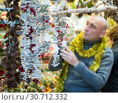 Adult man buys decorations for the Christmas tree on the street market. Стоковое фото, фотограф Яков Филимонов / Фотобанк Лори
