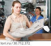 Купить «Woman receiving clothes after dry cleaner», фото № 30712372, снято 9 мая 2018 г. (c) Яков Филимонов / Фотобанк Лори