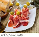 Купить «Rolled up dry-cured ham slices with olives», фото № 30712708, снято 23 сентября 2019 г. (c) Яков Филимонов / Фотобанк Лори