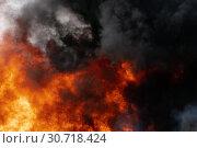 Купить «Сильный пожар, языки пламени и черный ядовитый дым в небе. Расфокусировка, размытость изображения», фото № 30718424, снято 18 апреля 2019 г. (c) А. А. Пирагис / Фотобанк Лори