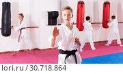 Купить «Preteen boy practicing karate movements with male trainer supervision», фото № 30718864, снято 3 июля 2020 г. (c) Яков Филимонов / Фотобанк Лори