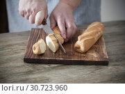 Купить «hands cut bread on wooden background», фото № 30723960, снято 26 марта 2019 г. (c) Майя Крученкова / Фотобанк Лори