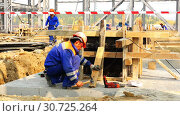 The builder in a robe and helmet secures the support for the foundation formwork (2016 год). Редакционное видео, видеограф Aleksandr Sulimov / Фотобанк Лори