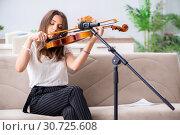 Купить «Female beautiful musician playing violin at home», фото № 30725608, снято 1 октября 2018 г. (c) Elnur / Фотобанк Лори