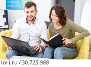 Friendly young woman and man relaxing in cozy hostel lobby, spending time with laptop and book. Стоковое фото, фотограф Яков Филимонов / Фотобанк Лори