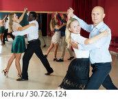 Купить «Positive adult couples dancing tango together in modern studio», фото № 30726124, снято 4 октября 2018 г. (c) Яков Филимонов / Фотобанк Лори