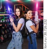 Купить «Two girls standing back and holding guns during laser tag game i», фото № 30726232, снято 23 августа 2018 г. (c) Яков Филимонов / Фотобанк Лори