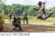 Dynamic paintball battle. Portrait female player jumping and aiming marker. Стоковое фото, фотограф Яков Филимонов / Фотобанк Лори