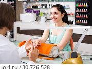 Купить «Manicurists giving manicure to female clients at nail salon», фото № 30726528, снято 28 апреля 2017 г. (c) Яков Филимонов / Фотобанк Лори