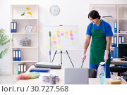 Купить «Male handsome professional cleaner working in the office», фото № 30727568, снято 7 января 2019 г. (c) Elnur / Фотобанк Лори