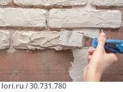 Штукатур работает вручную шпателем и ровняет штукатурку на стене. Стоковое фото, фотограф Иванов Алексей / Фотобанк Лори