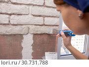 Девушка вручную штукатурит кирпичи на стене. Стоковое фото, фотограф Иванов Алексей / Фотобанк Лори