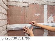 Девушка рисует на стене линии для точного расположения кирпичей. Стоковое фото, фотограф Иванов Алексей / Фотобанк Лори