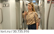 Купить «Young woman with a smartphone and headphones enters a subway car», видеоролик № 30735916, снято 25 апреля 2019 г. (c) Яков Филимонов / Фотобанк Лори