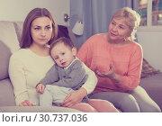 Купить «Adult female with her mother are having disagreements for parenting child», фото № 30737036, снято 15 февраля 2018 г. (c) Яков Филимонов / Фотобанк Лори