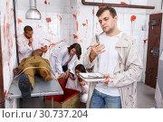 Купить «Young man in quest room with bloody traces», фото № 30737204, снято 8 октября 2018 г. (c) Яков Филимонов / Фотобанк Лори