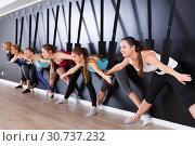 Купить «Girls practicing wall yoga with straps in studio», фото № 30737232, снято 29 января 2018 г. (c) Яков Филимонов / Фотобанк Лори