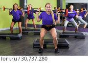 Girls in blue T-shirts performing deadlift exercise with bars. Стоковое фото, фотограф Яков Филимонов / Фотобанк Лори