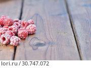 Купить «A handful of frozen raspberry berries lie on a wooden background on the left side», фото № 30747072, снято 27 июля 2018 г. (c) easy Fotostock / Фотобанк Лори